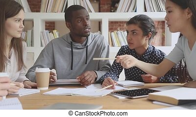 Focused indian student pointing at paper notes, preparing for college examinations with multiracial groupmates. Concentrated mixed race friends working on research project together in library.