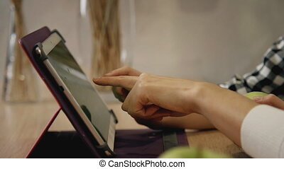 Woman and little girl touching display on tablet screen -...