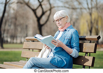Concentrated old woman reading a book