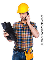 Concentrated on work. Confident young male carpenter in hardhat talking on mobile phone and looking at his clipboard while standing against white background
