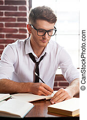 Concentrated on work. Confident young man in shirt and tie writing something in note pad while sitting at his working place