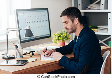 Concentrated on work. Side view of confident young man writing something in his notebook while sitting at his working place in office