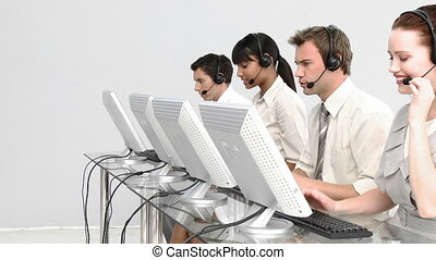 Concentrated people working in a call centre against a white...