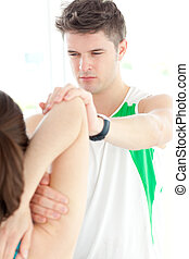 Concentrated physical therapist checking a woman's shoulder