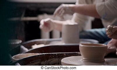 Concentrated potter making ceramics in workshop studio -...