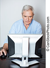 Concentrated Senior Man Using Computer In Class