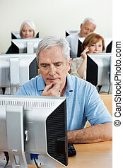 Concentrated Senior Man Using Computer In Classroom