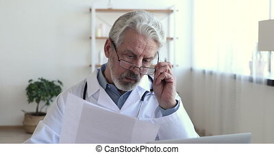 Concentrated serious old doctor reading medical papers analyzing report