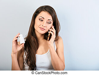 Concentrated serious young woman holding tablet bottle in ...