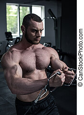 Concentrated shirtless bodybuilder training with weight machine at gym