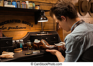 Concentrated shoemaker in workshop making shoes - Picture of...