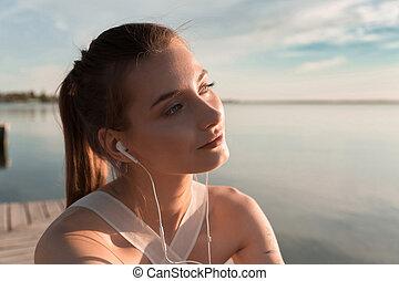 Concentrated sports lady at the beach listening music