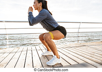 Concentrated sportswoman doing exercises with a rubber band