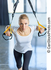 concentrated sportswoman training with resistance band in...