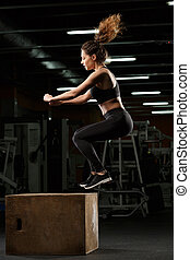 Concentrated strong sports lady make sport exercises jumping