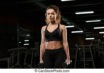 Concentrated strong sports lady make sport exercises with dumbbells