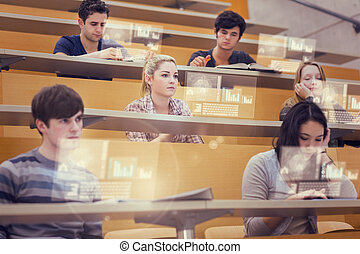 Concentrated students in lecture hall working on their...