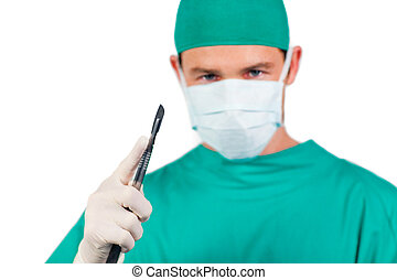 Concentrated surgeon holding a scalpel isolated on a white...