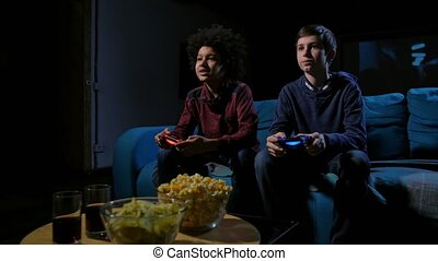 Concentrated teen gamers playing home console - Two diverse...