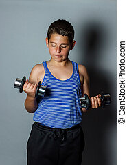 concentrated teenager boy lifting dumb bell