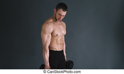 Concentrated topless bodybuilder performing biceps exercise...