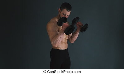 Concentrated topless bodybuilder performing biceps exercise with dumbbells. Slow motion