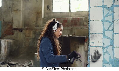 Concentrated woman is decorating old damaged column inside abandoned industrial building with graffiti using spray paint and listening to music with headphones.