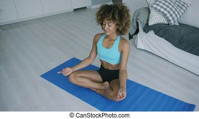 Concentrated woman practicing yoga on mat - Beautiful...
