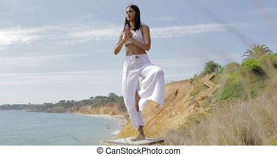 Concentrated woman practicing yoga - Stylish young model in...