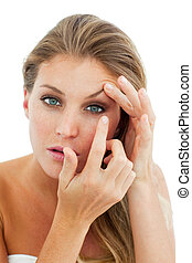 Concentrated woman putting a contact lens