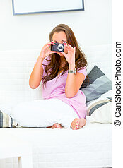 Concentrated woman sitting on couch at home and holding camera in hands