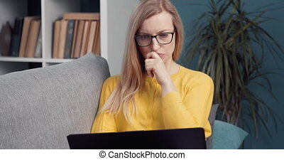 Concentrated woman working on laptop at home