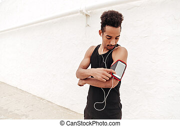 Concentrated young african sports man listening music.