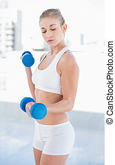 Concentrated young blonde model exercising with dumbbells
