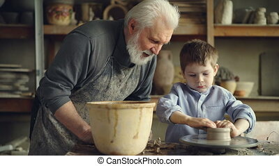 Concentrated young boy is molding clay into ceramic pot on spinning throwing wheel and his experienced grandfather is talking to him. Pottery and family tradition concept.