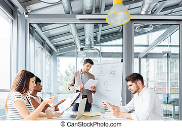 Concentrated young businessman giving presentation in office