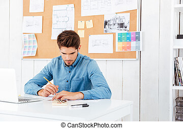 Concentrated young businessman sitting and writing at the table