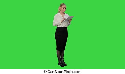 Concentrated young businesswoman using digital tablet present a project on a Green Screen, Chroma Key.