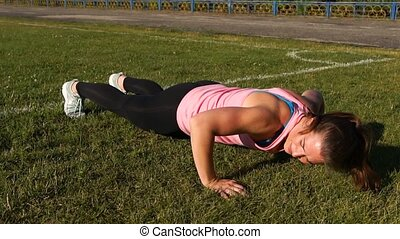 Concentrated Young Female Doing Push Ups in a Park