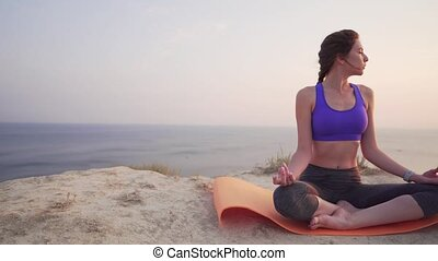 Concentrated young girl meditates with closed eyes at...