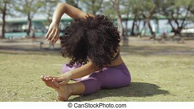 Concentrated young girl stretching body on lawn - Relaxing...