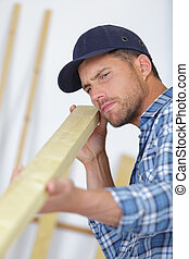 concentrated young male carpenter checking board