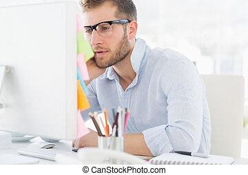 Concentrated young man using computer in a bright office