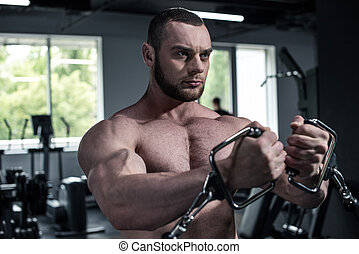 Concentrated young shirtless bodybuilder training with weight machine at gym