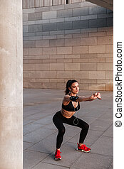 Concentrated young sports lady make sport exercises