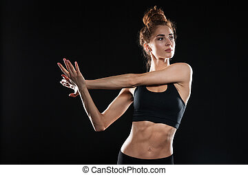 Concentrated young sports lady make stretching exercises.