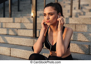Concentrated young sports lady with earphones outdoors.