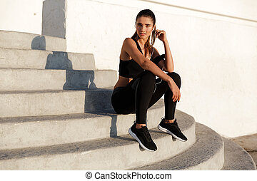 Concentrated young sports woman listening music