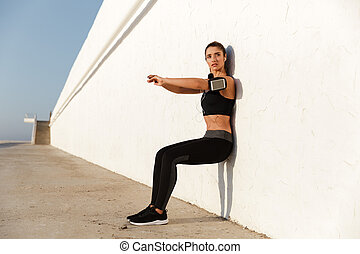 Concentrated young sports woman listening music make sport exercises