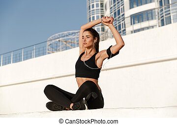 Concentrated young sports woman make sport stretching exercises.